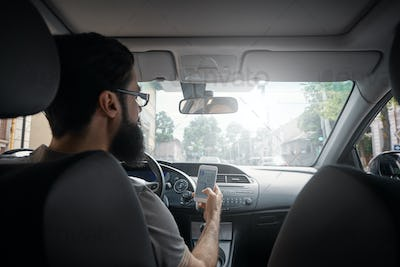 Man using mobile phone while driving.