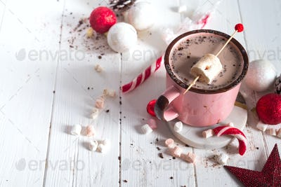 Enamel cup of hot cocoa with mini marshmallows and candy canes with pine