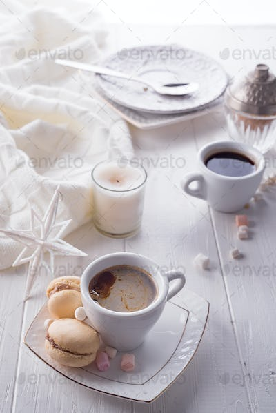 Tasty sweet macarons and coffee cup on white wooden background. Cristmas concept lazy morning