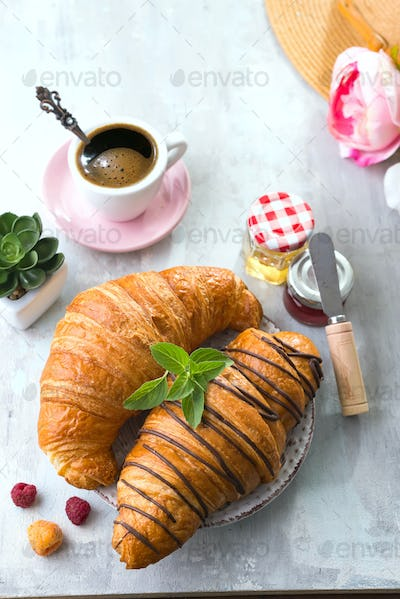 Fresh Croissant with berries and jam for breakfast, hat and flowers on white