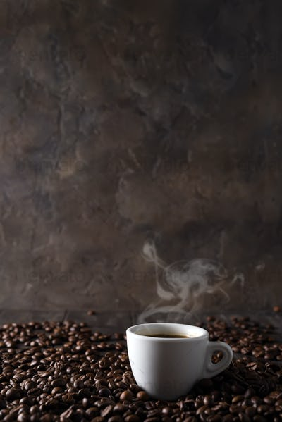 cup of hot coffee on the background of coffee grains on a dark wooden background, copy space