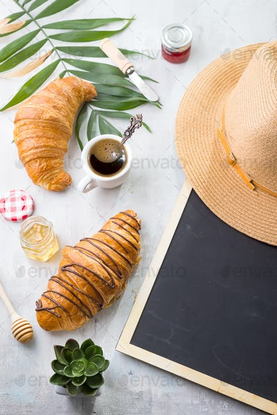 Traveled breakfast with croissants, honey, jam and berries on the trip. Background of a chalkboard