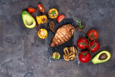 Grilled chicken steak and vegetable , baked potatoes and corn on dark background