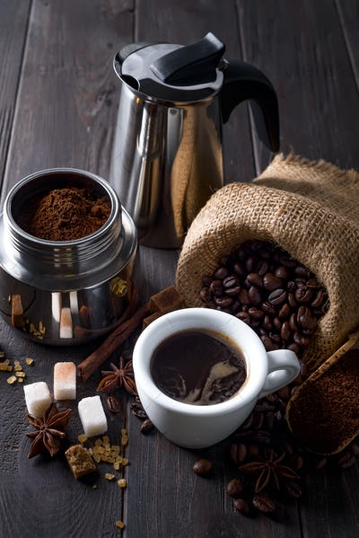ground coffee is filled with a geyser coffee maker and cup of coffee wit spices on a wooden table