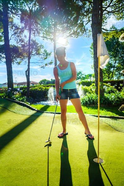 Mini Golf - Woman playing Golf on green grass at sunset