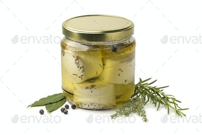 Jar with preserved white organic Dutch goat cheese and fresh her