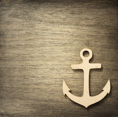 toy anchor at wooden background