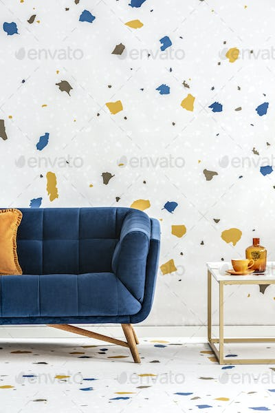 Blue sofa with orange pillow next to table in colorful living ro