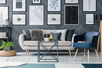 Blue armchair next to sofa and table in living room interior wit