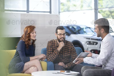 Car dealer showing an offer to his happy clients in a car showro