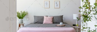 Grey and pastel pink bedding on double bed with coffee cup in re