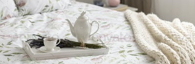 Real photo of white tray with tea cup, porcelain jug and fresh l
