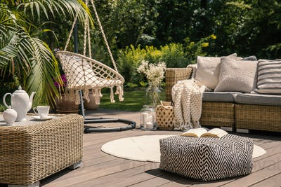 Pouf on wooden terrace with rattan sofa and table in the garden