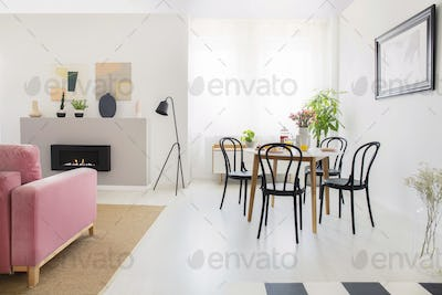 Black chairs at wooden table in white apartment interior with la
