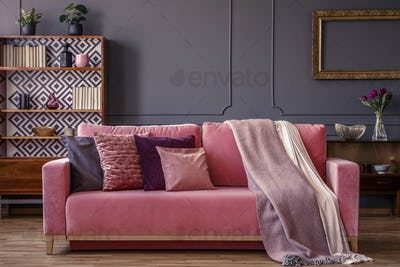 Cushions and blankets on a pink velvet sofa in a luxurious gray