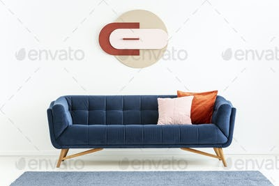 Pink and orange pillows on blue sofa in white apartment interior