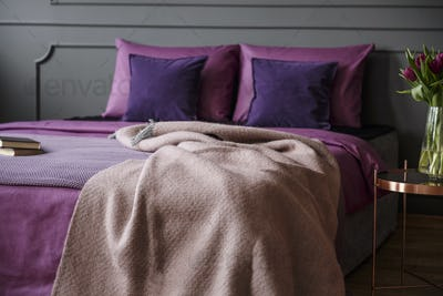 Real photo of modern hotel bedroom interior with pink blanket on