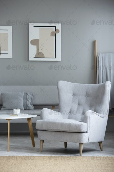 Grey armchair next to table in living room interior with posters