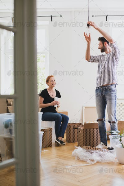 Man hanging a lamp while furnishing new home with his smiling wi