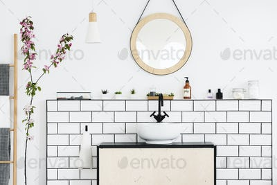 Real photo of a bathroom interior with a round mirror, sink with