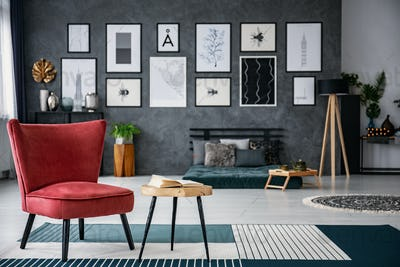 Red armchair next to table on carpet in dark grey living room in