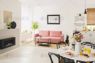 Flowers at table in white apartment interior with poster above p