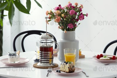 Real photo of white dining table with fresh flowers in ceramic v