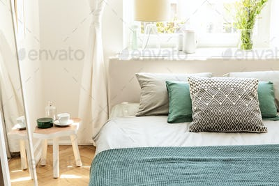 Pillows and green sheets on bed in bedroom interior with white t