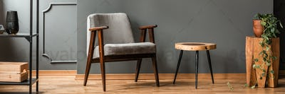 Grey armchair standing by a handmade end table in dark living ro