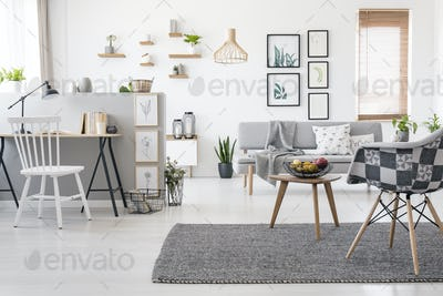 Checkered, stylish chair on a gray rug in a spacious, scandinavi