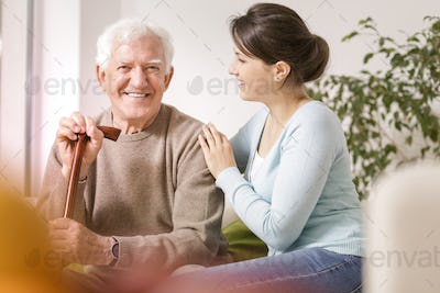Smiling grandfather with walking stick and happy woman during me