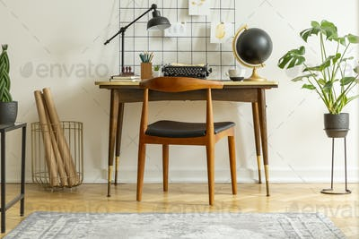 Plant next to chair and desk with lamp typewriter and globe in c