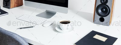 Close-up on a cup of coffee next to a computer mouse and keyboar