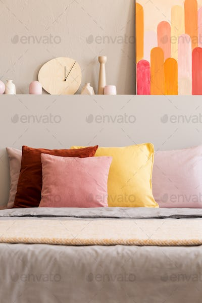Real photo of bed with colorful pillows in bright room interior