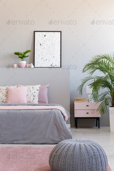 Grey pouf next to bed with cushions in modern bedroom interior w