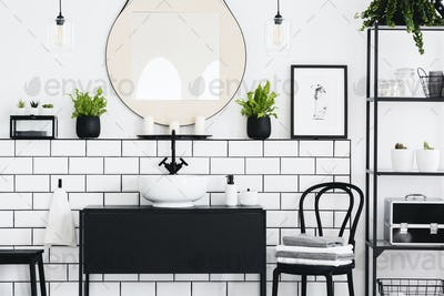 Real photo of black and white bathroom interior with a mirror, c