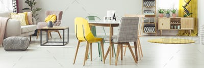 Yellow and grey chair at dining table in apartment interior with