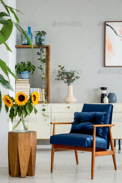 Sunflowers on wooden stool next to blue armchair in living room