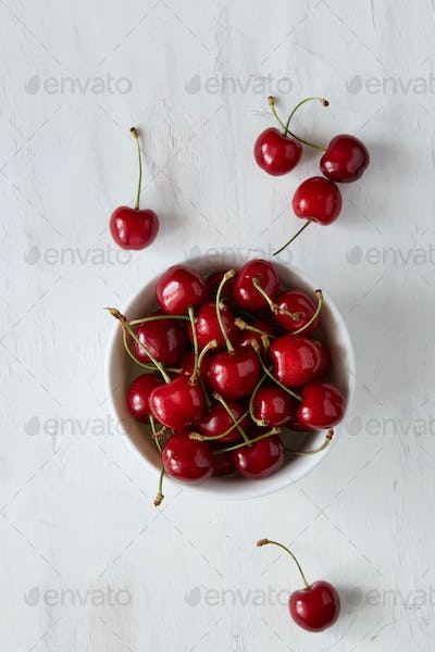 Some sweet cherries with green stems and leaves in the white ceramic bowl on the white background