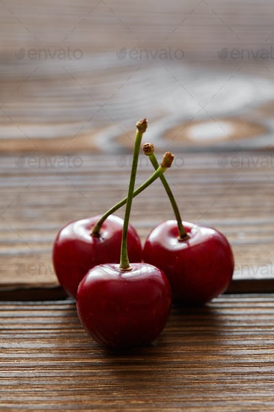 Some sweet cherries with green stems on wooden background