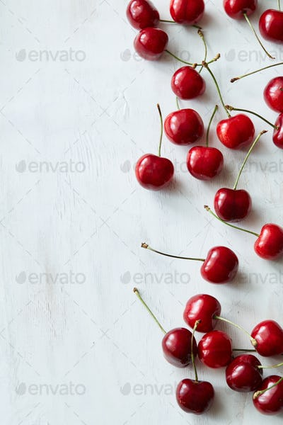 Scattered sweet cherries on white vintage background with copy space