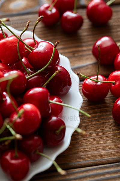 A lot of sweet cherries in the white vintage plate on the sackcloth and wooden table