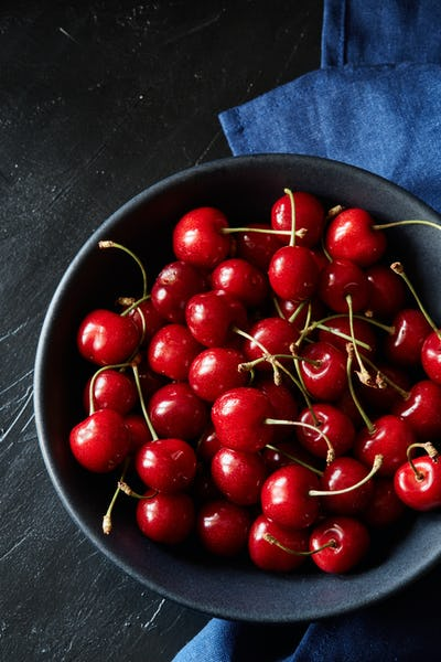 A lot of sweet cherries in the black ceramic bowl on the black tablecloth
