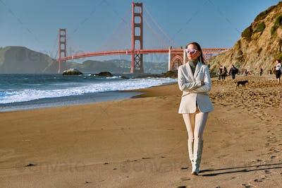 Woman walking on beach near Golden Gate Bridge