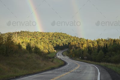 Double rainbow above road curving through hills in northern Minn