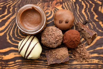 Handmade chocolate candies and jar of chocolate paste on wooden
