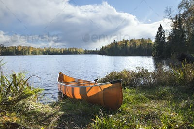 Backlit canoe on shore of northern Minnesota lake during autumn