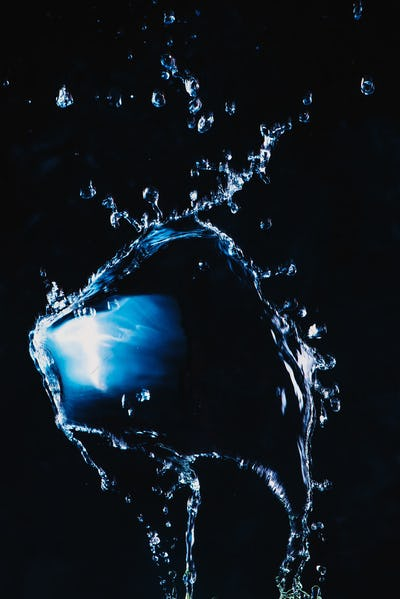 Dynamic splash of water on a dark background. Flying transparent liquid with a shiny surface. High