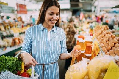 Portrait of beautiful woman holding shopping basket at marketplace