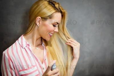 Woman spraying hairspray on beautiful long hair